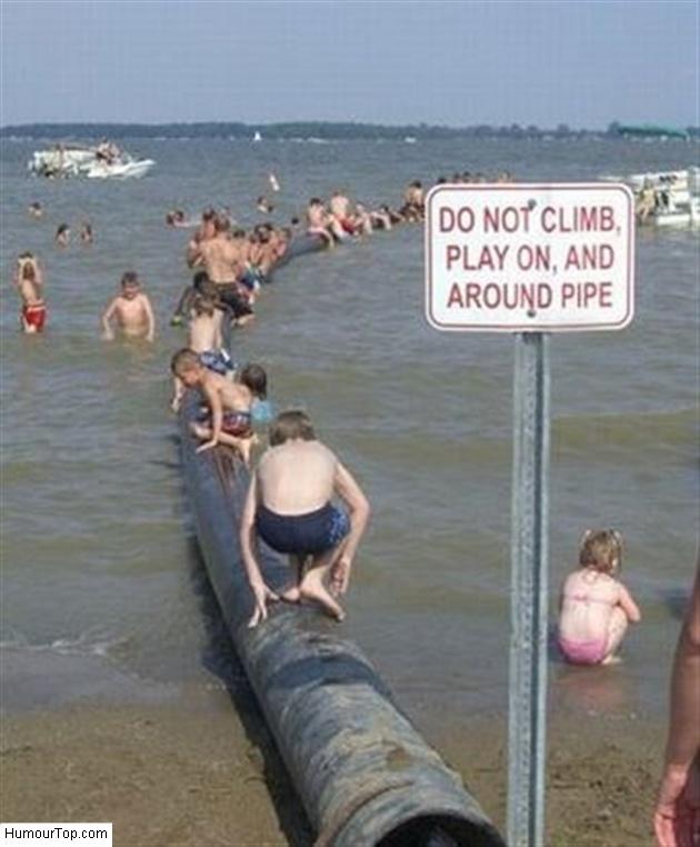 Panneau qui interdit aux enfants de jouer à côté des égouts qui s'écoulent dans la mer